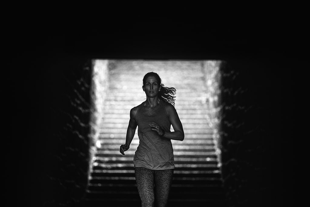 An adult woman training on a large set of outdoor steps, running and employing other stairway exercise variations. High contrast black and white image of her running through a tunnel at the bottom of the stairway.